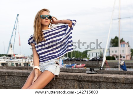 Young woman with old camera sitting on pier near sea. Outdoor, lifestyle