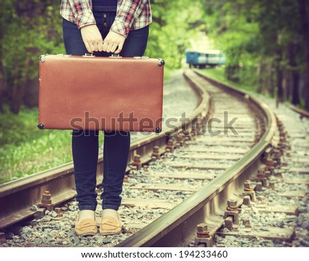 young woman with old suitcase on railway, departing train on background, retro stylized - stock photo