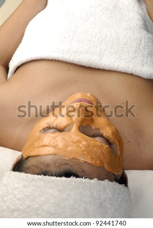 Young woman with orange facial mask,facial treatment on a spa. - stock photo
