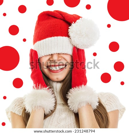 Young woman with oversize Christmas hat and gloves smiling covering her eyes and ears isolated on white background with red dots. Closeup studio shot of cute teenage girl with knitted Santa Claus hat. - stock photo