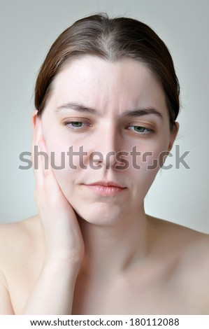 Young woman with painful facial expression - stock photo