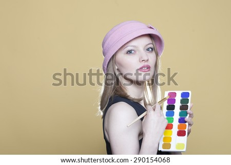 Young woman with paint and brush on beige background - stock photo