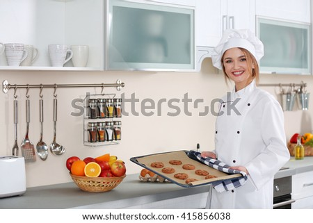 Young woman with pan of chocolate cookies in the kitchen