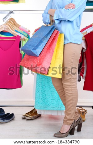 Young woman with paper bags near rack with hangers