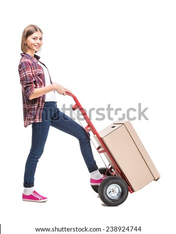 Young woman with paper box and a hand truck, isolated on white background. - stock photo
