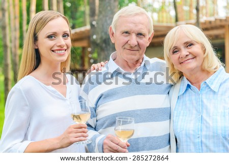 Young woman with parents. Happy young woman bonding to her senior parents while standing outdoors together  - stock photo