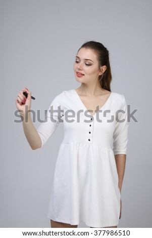 young woman with pen on grey background - stock photo