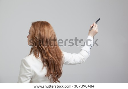 young woman with pen  writes or shows on grey background - stock photo