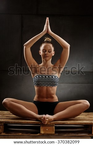 Young Woman With Perfect Body Practicing Yoga Sitting On Pallet In Studio