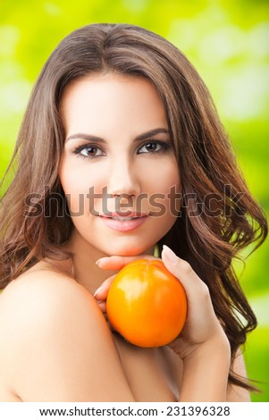 Young woman with persimmon fruit, outdoors - stock photo