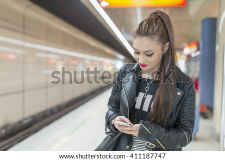Young woman with phone in subway.