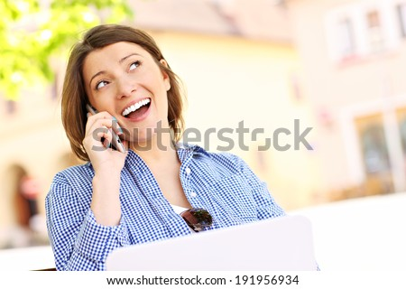 Young woman with phone sitting on a bench - stock photo
