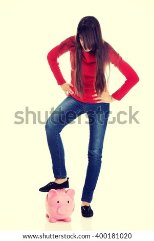 Young woman with piggybank under leg. - stock photo