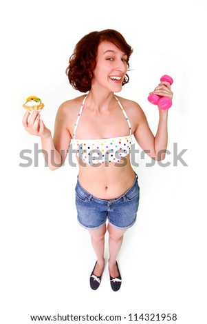 Young woman with pink dumbbells and fruit cake - stock photo