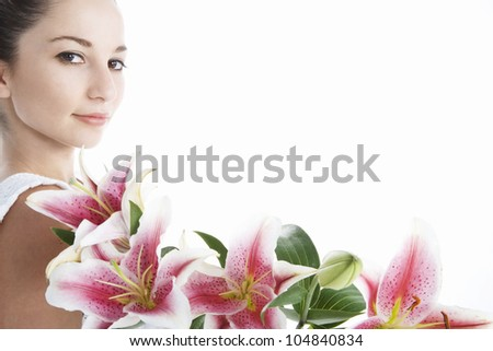Young woman with pink japanese lilies framing the background. - stock photo