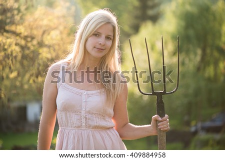 Young woman with pitchfork - stock photo