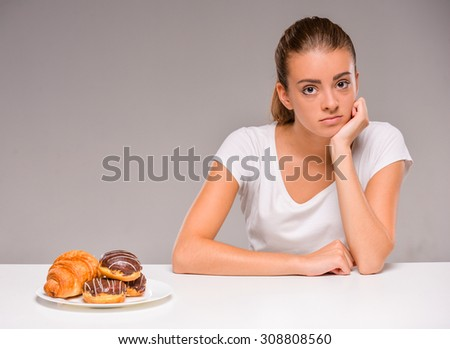 Young woman with plate of sweets. Concept of diet. Healthy food. - stock photo