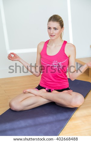 Young woman with ponytail wearing pink sleeveless top and black shorts stretches her arms while seated on a yoga mat near wood stairs