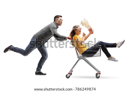 Young woman with popcorn and 3D glasses riding inside a shopping cart being pushed by a young man with 3D glasses isolated on white background