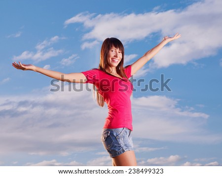Young woman with raised arms outdoor