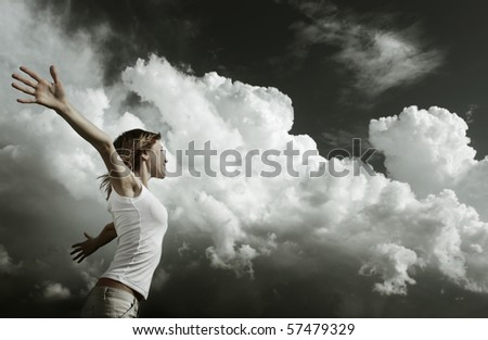 Young woman with raised hands over stormy clouds background - stock photo