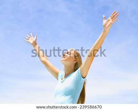 Young woman with raised hands standing on wet sand - stock photo