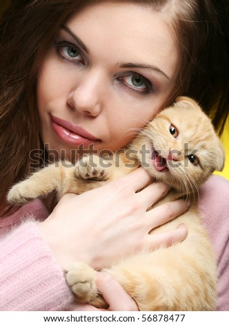 Young woman with red England lop-eared kitten - stock photo