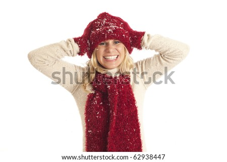 Young woman with red hat and scarf throwing snow