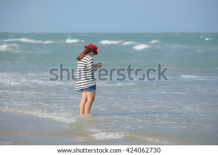 Young woman with red hat standing in the sea while using a smart phone