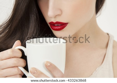 young woman with red lips holding a white cup, closeup
