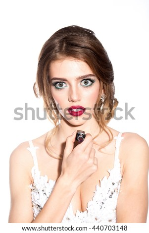 Young woman with red lips on pretty emotional face in elegant dress holding makeup lipstick in studio isolated on white background