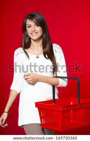 Young woman with red shopping basket, red background - stock photo