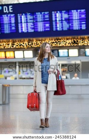 Young woman with red suitcase at international airport, going to the gate and waiting for her flight. Female passenger at terminal, indoors. - stock photo