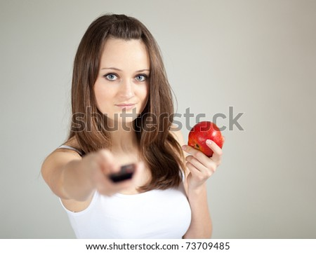 Young woman with remote control and apple
