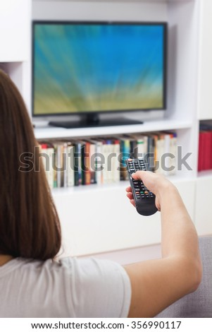 Young woman with remote control, watching TV program at home,
