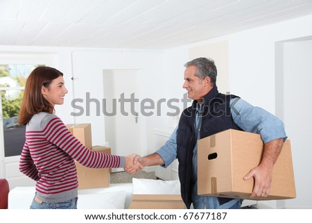 Young woman with removal man holding boxes - stock photo
