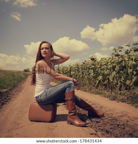 Young woman with retro suitcase traveling in countryside, summer nature outdoor, toned