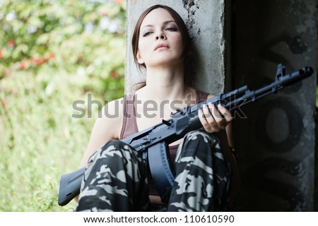 Young woman with rifle (Kalashnikov AK-74) - stock photo