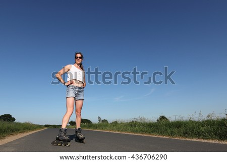 Young woman with rollerskates on a road - stock photo