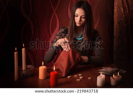 Young woman with runes and divination cards in room - stock photo