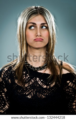Young Woman with Sad Expression over a Grey Background - stock photo