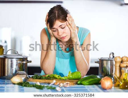 Young woman with sad face cooking dinner at home interior - stock photo