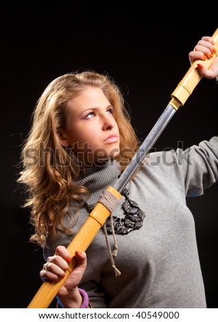 Young woman with samurai sword. On dark background.