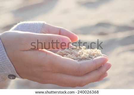 Young woman with sand in hands. - stock photo