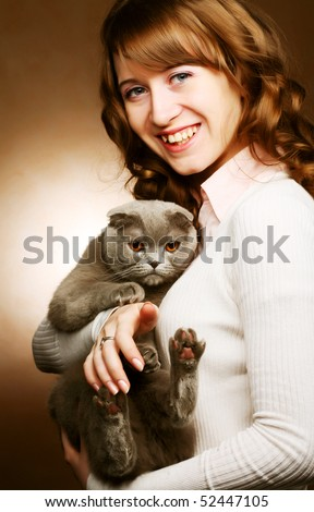 Young woman with scottish-fold cat.On brown background. - stock photo