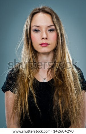 Young Woman with Serious Expression over a Grey Background