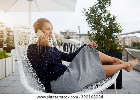Young woman with serious face is phoning via mobile phone, while is sitting in comfortable chair in cafe terrace. Attractive female is calling via cell telephone during her leisure time in weekend - stock photo