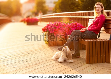 Young woman with shih-tzu dog sitting on bench on wooden bridge in europe town. Red sunset light. - stock photo