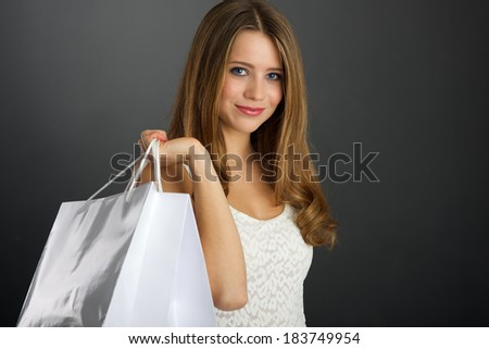 Young woman with shopping bag on dark background