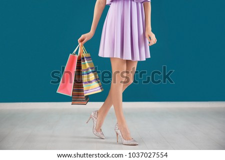Young woman with shopping bags against color wall